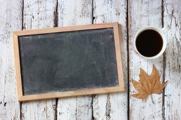 top view image of empty blackboard next to cup of coffee , over wooden table.