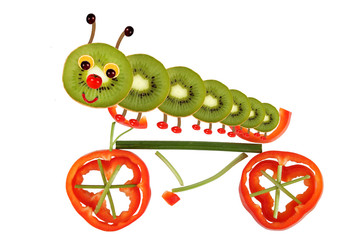 Creative food concept. Funny little caterpillar on a bicycle ma