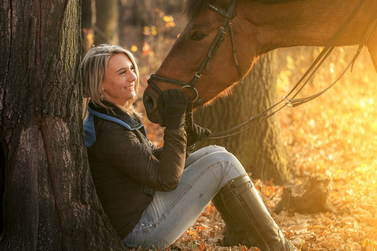 Beautiful young girl with horse in autumn sunset