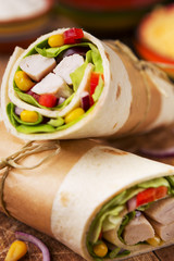 Healthy chicken wraps on a rustic chopping board