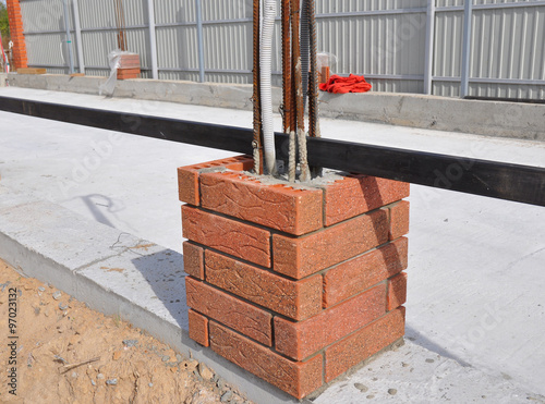 Closeup On Building New Fence Column With Bricklaying Light Wires And Iron Bar Whether