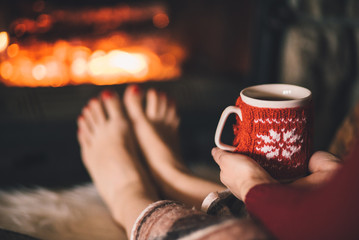 Bare woman feet by the cozy fireplace. Woman relaxes by warm fire with a cup of hot drink and warming up her feet. Close up on feet. Winter and Christmas holidays concept