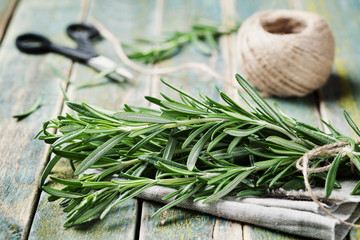 Bunch of rosemary on wooden table, rustic style, fresh organic herbs