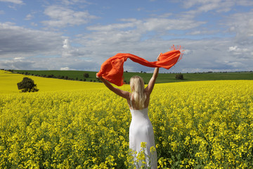 Happy woman flailing scarf in a field of flowering canola in spr