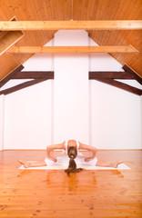 Woman practicing Yoga in a Studio..