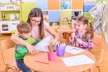 kindergarten teacher and kids on creative activities