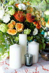 The big white candles on flowers background. A wedding composition, an ornament