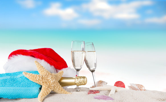 Champagne flutes with santa cap on sunny beach.