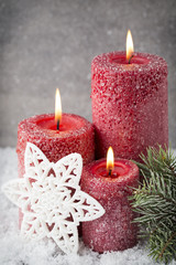 Three red candles on gray background, Christmas decoration. Adve
