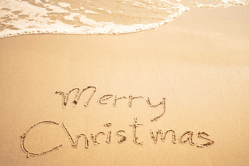 merry christmas written on the beach
