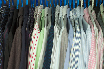 A collection of men's striped shirts, are hung orderly on a clothes rack of a closet.