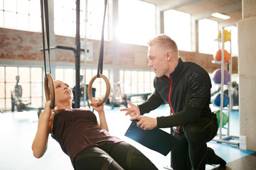 Male instructor helping a woman during workout