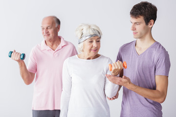 Fitness seniors exercising with trainer