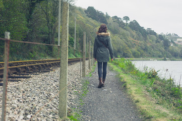 Young woman walking by railway tracks