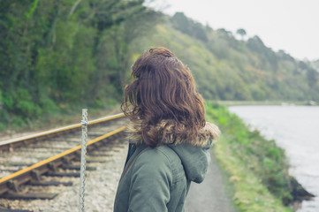 Young woman standing by railway tracks