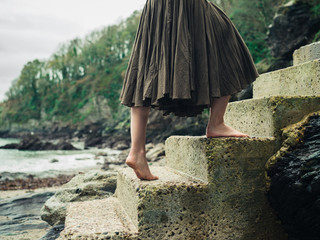 Barefoot woman walking up steps in nature