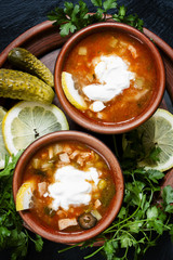 Home Russian meat hodgepodge (solyanka) with sour cream in a cla