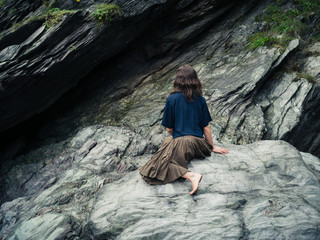 Young woman sitting on rock outside cave