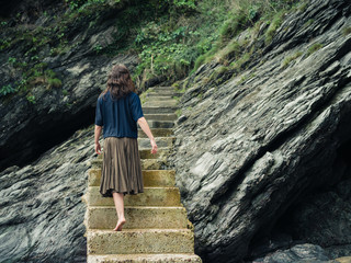 Young woman walking up steps by cliff