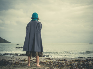 Young barefoot woman with headscarf on beach