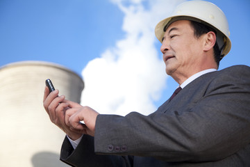 Businessman texting at power plant