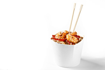 Delicious seafood wok noodles box with shrimps and udon with chopsticks. Chinese and asian takeaway fast food. Studio isolated with real shadow
