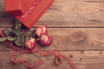 Red gift box and bouquet of roses on wooden background