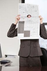 Woman smiling through hole in newspaper