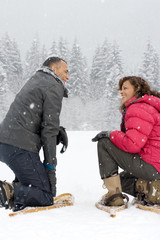 Couple crouching in the snow wearing snowshoes
