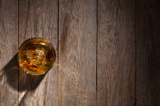 Glass of whiskey with ice on wood