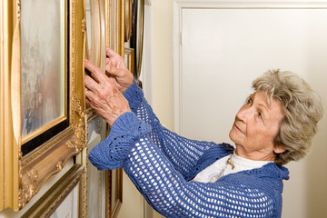 Woman adjusting picture frames