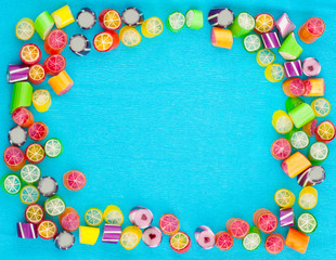 mixed colorful fruit candies on blue background with space for text