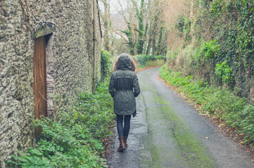 Person wearing winter coat walking in countryside