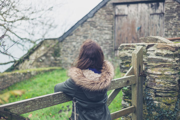 Young woman by gate outside barn