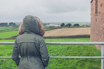 Person in winter coat by field