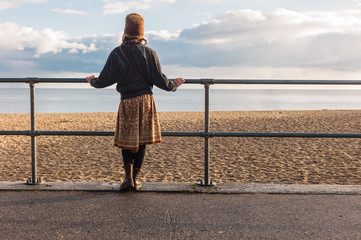 Woman standing by railings on beach