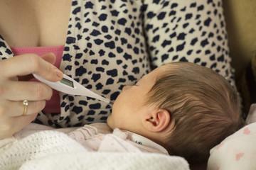 mum checking babies temperature