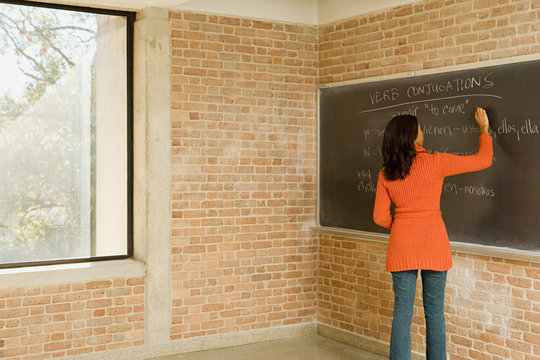 Teacher writing Spanish text on blackboard