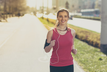 Young beautiful woman running in the city