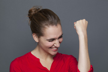 winning behavior concept - passionate 20s girl laughing and gesturing for successful achievement and motivation,studio shot on gray background