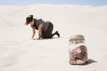 Woman searching for jar of coins in desert