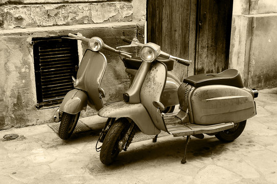 Two vintage scooter parked in the street
