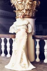Fashion portrait of beautiful woman in long white dress in an ol