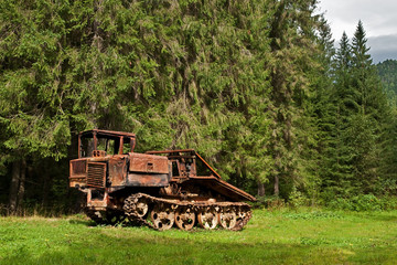 abandoned skidder against the backdrop of an ancient mountain forest