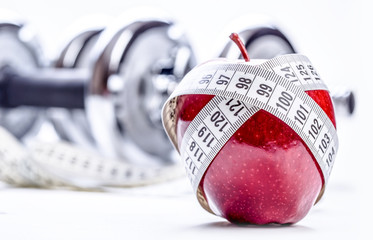 Fresh red apple, tape measure, and in the background Fitness dumbbells. Healthy lifestyle diet and exercise. Studio shot.