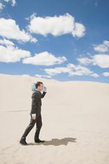 Businessman in desert with bottle