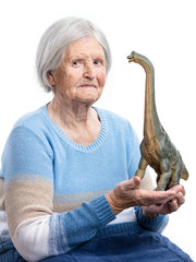 Portrait of a senior woman holding a toy dinosaur over white background, aging concept, humorous aspect