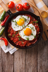 huevos rancheros closeup in the pan and ingredients, vertical top view