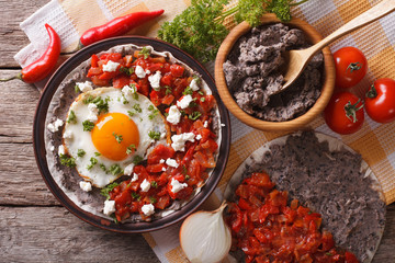 Mexican huevos rancheros on the plate closeup. horizontal top view