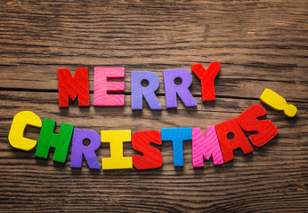 Merry Christmas written with colorful wooden letters, on old plank